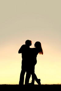 A silhouette of a happy young married couple slow dancing outside at sunset, with copy-space in sky.